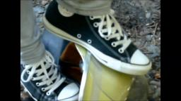 Jana tramples on a fire helmet and crushes it with her black chucks trailer