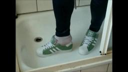 Jana tramples on bed with her shiny green Adidas Superstars and messes up both and then washes them