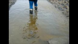 Jana goes in mud flat with zebra rubber boots and washes them in stream trailer