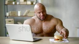 Huge weightlifter biting big BURGER sitting behind laptop indoor