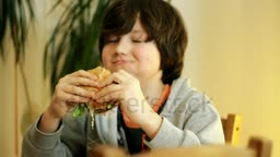 stock-footage-young-boy-eating-hamburger