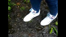 Jana walks with her Adidas Top Ten white patent with loop through the mud yt trailer